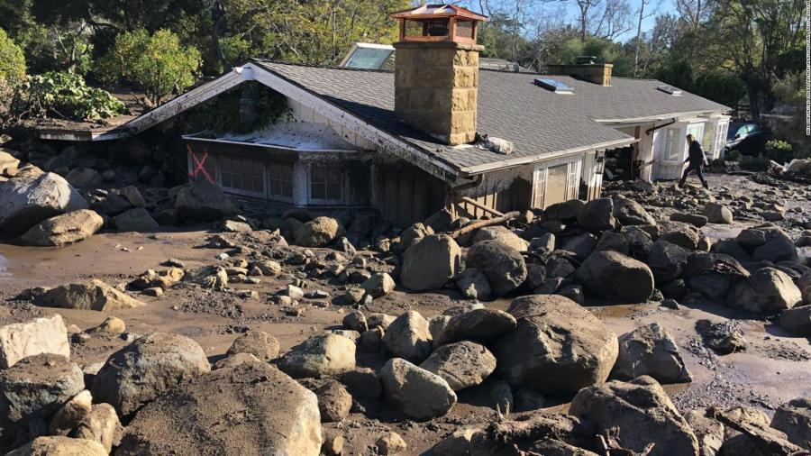 Jan 9, 2018 - Montecito, Santa Barbara County, California, U.S. - KERRY MANN navigates the large boulders and mudflow that destroyed the home of her friend in Montecito. The woman who lives in the home has not been seen since the early hours of Tuesday. At least 15 people died and thousands fled their homes in Southern California as a powerful rainstorm triggered flash floods and mudslides on slopes where a series of intense wildfires had burned off protective vegetation last month.  (Newscom TagID: zumaamericasnineteen760940.jpg) [Photo via Newscom]
