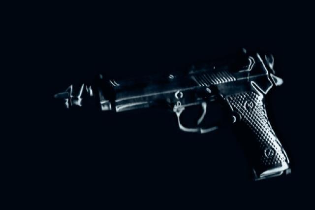 Bullet emerging from a handgun, on black